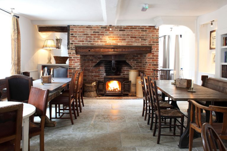 The dining room with a roaring fire at The Black Lion Hotel in Walsingham.