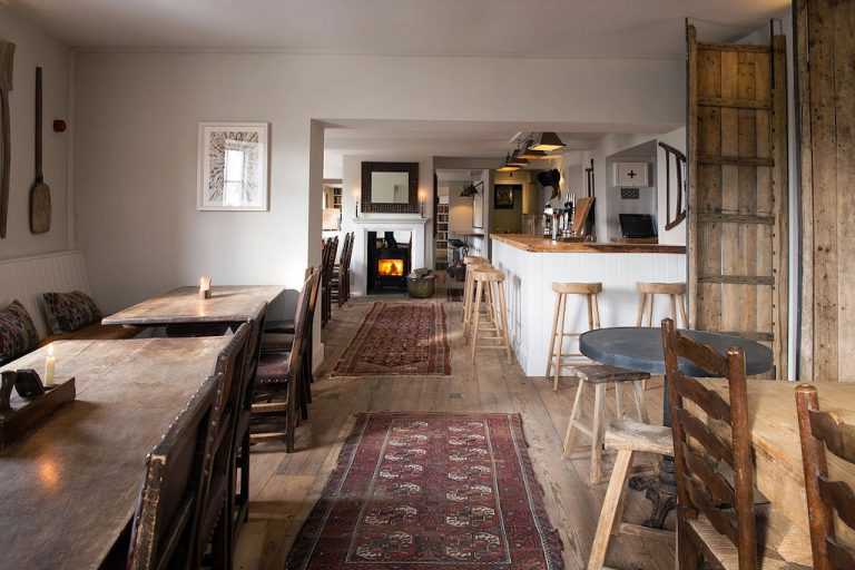 The dining room and bar with a roaring fire at The Carpenters Arms in Wighton.