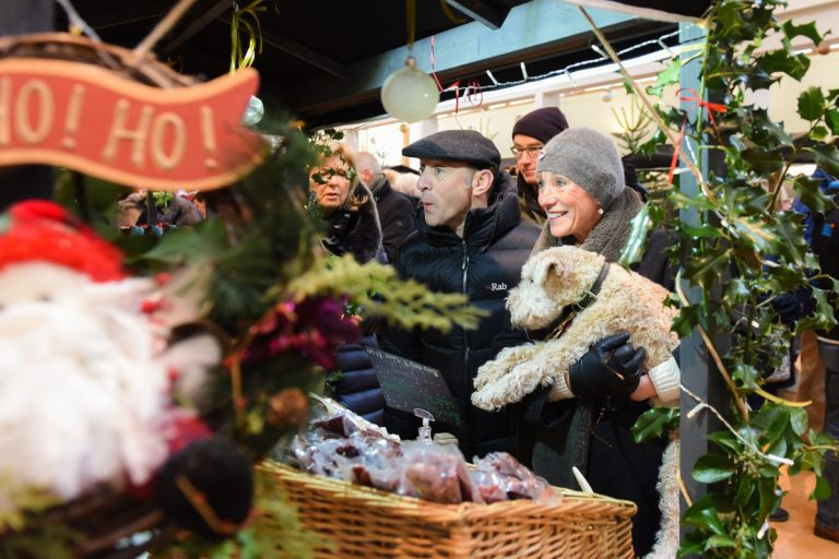 Customers shopping at a stall during a Christmas Fair.