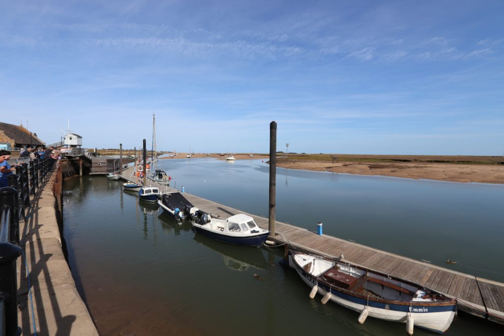 Boats moored along the jetty at Wells harbour.